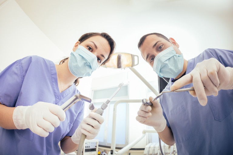 Cheerful Dentists Holding Dental Tools Looking at Camera. Personal or Patient Point of View, POV. They are holding Drill, Mirror, Aspirator and Spreader.